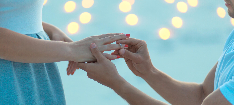 女性の指に指輪をはめているカップルの画像